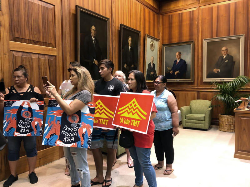 Opponents of a giant telescope planned for Hawaii's tallest mountain listen to a protest leader talk to reporters in the governor's office in Honolulu on Friday's Sept. 13, 2019. State officials are concerned about hateful language used on both sides of the heated debate over whether to build the Thirty Meter Telescope. (AP Photo/Jennifer Sinco Kelleher)