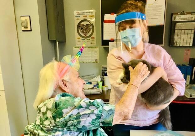 Crystal Massier from Eden Care Communities holds up Lorelai the cat for resident Liliann Wilton to pet. (Submitted by Crystal Massier - image credit)