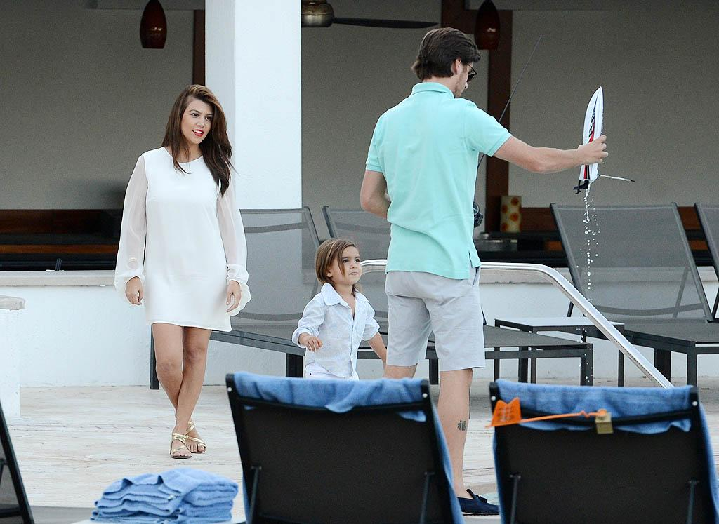 November 19, 2012: Kourtney Kardashian, Scott Disick, and their son Mason Disick play with a remote control boat at the Eden Roc Hotel pool in Miami Beach, FL.  PIctured here: Kourtney Kardashian, Mason Disick, Scott Disick