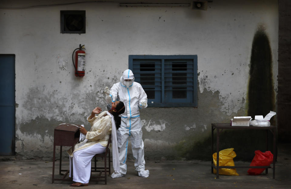 A health worker takes a nasal swab sample to test for COVID-19 in New Delhi, India, Tuesday, Sept. 1, 2020. India has now reported more than 75,000 infections for five straight days, one of the highest in the world, just as the government began easing restrictions to help the battered economy. (AP Photo/Manish Swarup)