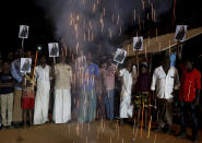 FILE - In this Jan. 20, 2021, file photo, villagers release firecrackers and hold placards featuring Vice President Kamala Harris after her inauguration, in Thulasendrapuram, the hometown of Harris' maternal grandfather, south of Chennai, Tamil Nadu state, India. (AP Photo/Aijaz Rahi, File)