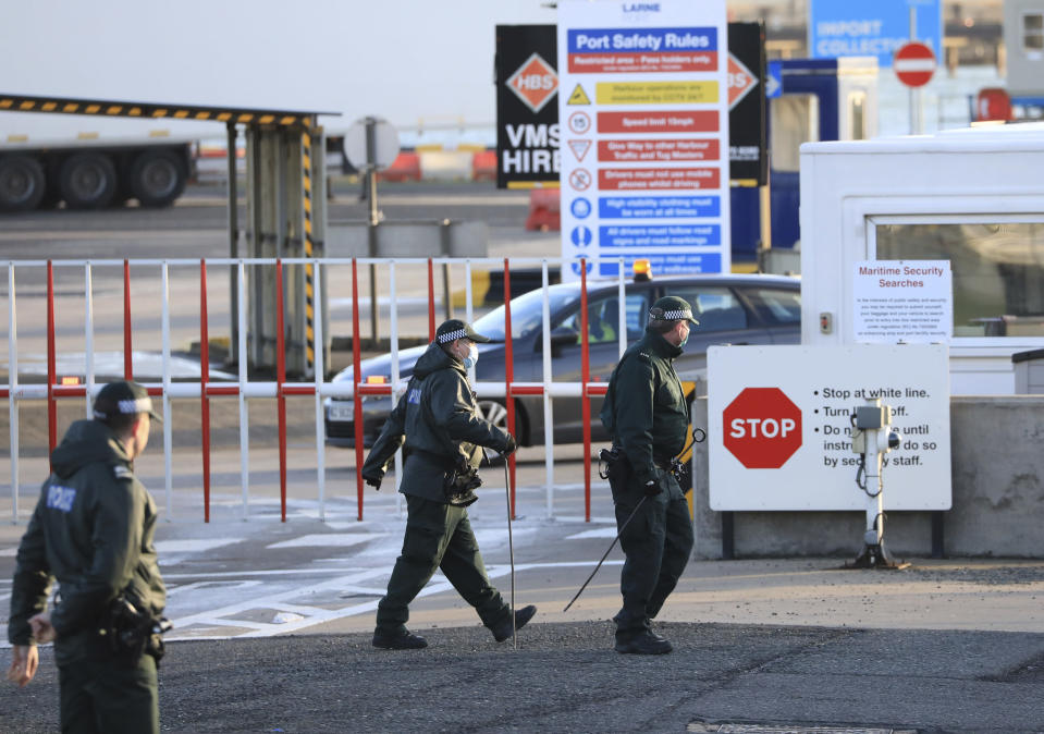 Police conduct a security sweep at the P&O ferry terminal in the port at Larne on the north coast of Northern Ireland, Friday, Jan. 1, 2021. This New Year's Day is the first day after Britain's Brexit split with the European bloc's vast single market for people, goods and services, and the split is predicted to impact the Northern Ireland border. (AP Photo/Peter Morrison)