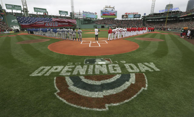 The Toronto Blue Jays, left, and Boston Red Sox stand along the base lines during the national anthem before the home opener baseball game, Tuesday, April 9, 2019, in Boston. (AP Photo/Charles Krupa)
