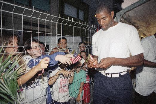 FILE - In this July 28, 1992, file photo, U.S. Olympic basketball player Magic Johnson signs autographs for local children in Barcelona, Spain. (AP Photo/Bill Sikes, File)