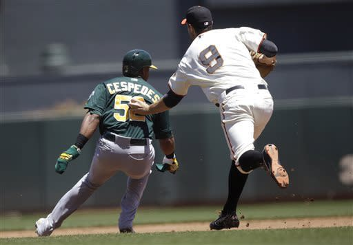 San Francisco Giants first baseman Brandon Belt (9) tags out Oakland Athletics' Yoenis Cespedes (52) on an attempted steal of second base during the third inning of a baseball game in San Francisco, Thursday, May 30, 2013. (AP Photo/Jeff Chiu)