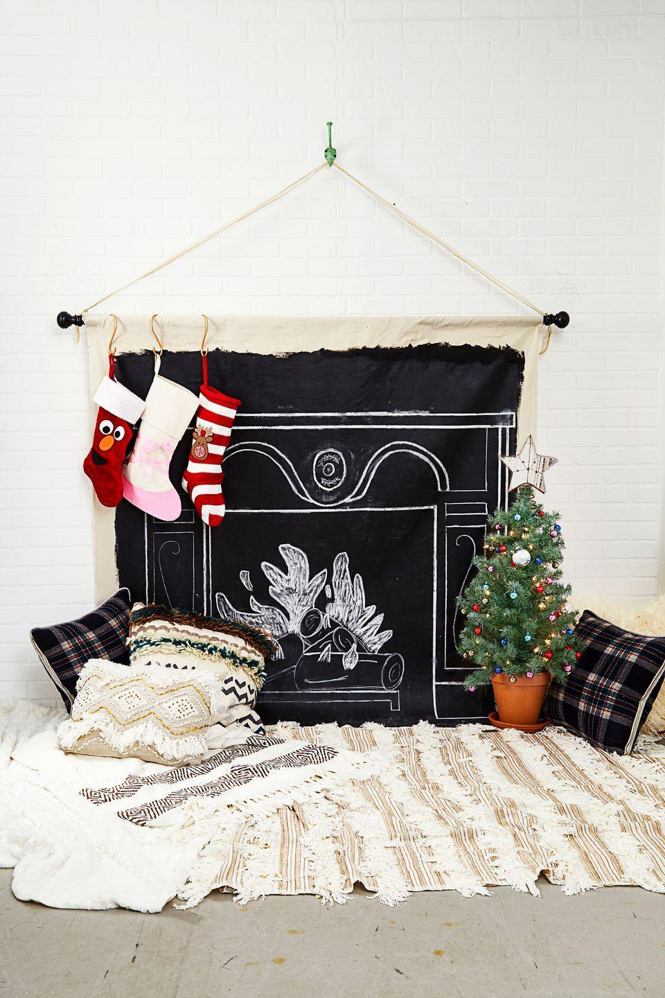 <p>Here's another way to fake the cozy fireplace experience. Draw a fake fireplace with painted chalk on canvas, hang your masterpiece from the wall, add stockings, and then surround it with floor cushions and blankets. This will be a total lifesaver if you live in a small apartment but still want to go big on the Christmas decor. Slide up a teeny tree for the full Christmas effect. </p>