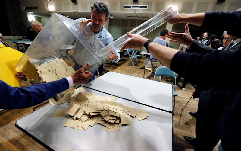 Officials empty a ballot box at the start of counting at a polling station in Tulle - Credit:  REGIS DUVIGNAU/REUTERS
