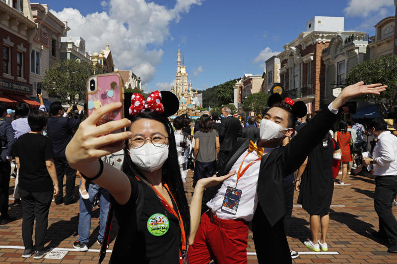 Visitors wearing face masks to prevent the spread of the new coronavirus, take a selfie at the Hong Kong Disneyland on Thursday, June 18, 2020. Hong Kong Disneyland on Thursday opened its doors to visitors for the first time in nearly five months, at a reduced capacity and with social distancing measures in place. The theme park closed temporarily at the end of January due to the coronavirus outbreak, and is the second Disney-themed park to re-open worldwide, after Shanghai Disneyland. (AP Photo/Kin Cheung)