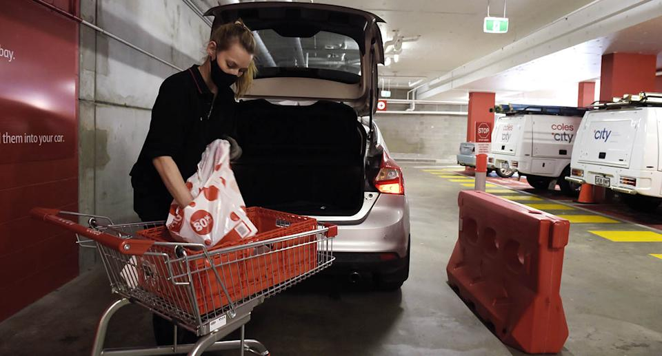 A woman loading a Coles Click and Collect order into a car. Source: Getty Images