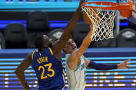 Golden State Warriors forward Draymond Green (23) defends against a shot-attempt by Charlotte Hornets guard LaMelo Ball during the first half of an NBA basketball game in San Francisco, Friday, Feb. 26, 2021. (AP Photo/Jeff Chiu)