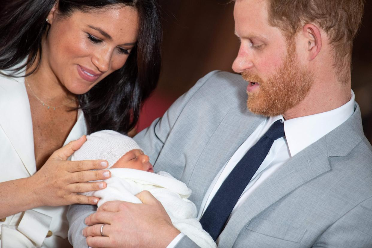 TOPSHOT - Britain's Prince Harry, Duke of Sussex (R), and his wife Meghan, Duchess of Sussex, pose for a photo with their newborn baby son, Archie Harrison Mountbatten-Windsor, in St George's Hall at Windsor Castle in Windsor, west of London on May 8, 2019. (Photo by Dominic Lipinski / POOL / AFP)        (Photo credit should read DOMINIC LIPINSKI/AFP/Getty Images)