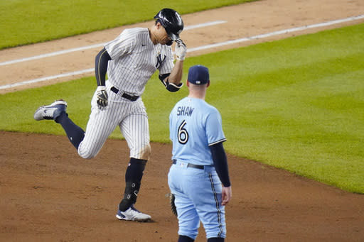 New York Yankees' Giancarlo Stanton, left, passes Toronto Blue Jays second baseman Travis Shaw as he runs the bases after hitting a home run during the fourth inning of a baseball game Thursday, Sept. 17, 2020, in New York. (AP Photo/Frank Franklin II)
