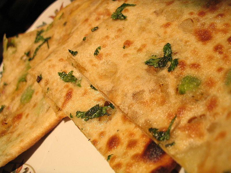 """<p>Though parathas are widely consumed all over India, Punjabis consider it their first love. Some families start their day with this dish as their breakfast. When combined with white butter, happiness rises to another level. Every family makes their parathas in their own home style but here's a simple recipe. Boil 4 – 5 potatoes and peel them. Mash them with a potato masher and add some finely chopped onions, green chilies, coriander, ginger, salt, red chili & jeera powder and some chaat masala. Give this all a good mix. Keep kneaded wheat dough ready. Pinch out a ball from the dough and roll it flat and put some potato stuffing in the centre with over an inch space from the circumference. Bring the edges of the dough together and make small dimsum shaped buns and flatten them with the rolling pin to the desired size. Pour 1-2 teaspoons of ghee on a hot tawa and gently place the paratha on it. Keep flipping the sides until cooked. """"Creative Commons Aloo Paratha"""" by Simon Law is licensed under CC BY 2.0 </p>"""
