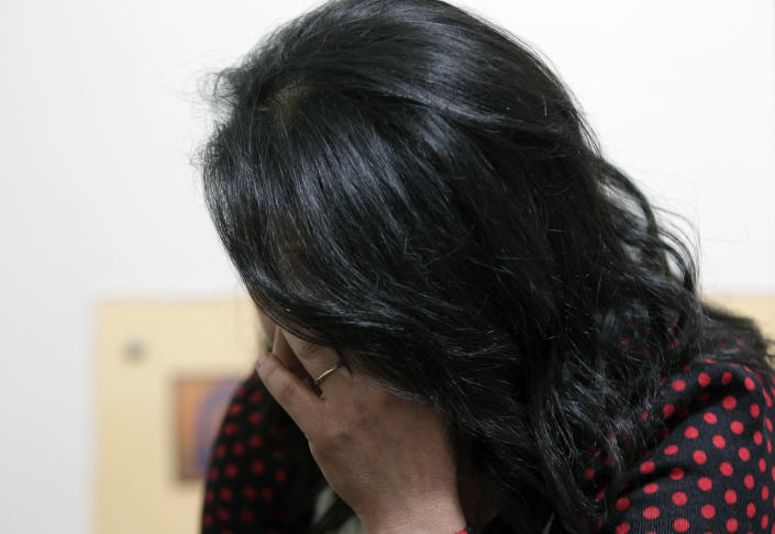 """In this Wednesday, Feb. 26, 2014 photo, a Lebanese woman, who only gave her first name as Bahiya, speaks while not showing her face for fear of reprisals, describes how her husband of nearly 20 years regularly beat her with his hands and a stick, during an interview with The Associated Press, in the office of the women's rights group Kafa in Beirut, Lebanon. With the help of Kafa, Arabic for """"Enough,"""" she was able to get a divorce recently and won custody of her four daughters. Although Lebanon appears very progressive on women rights compared to other countries in the Middle East, domestic violence remains an unspoken problem and the nation's parliament has yet to vote on a bill protecting women's rights nearly three years after it was approved by the Cabinet. (AP Photo/Bilal Hussein)"""