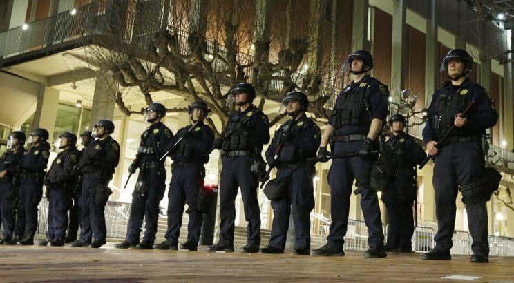 In this Feb. 1, 2017 file photo, University of California, Berkeley police guard the building where Breitbart News editor Milo Yiannopoulos was to speak. (Photo: Ben Margot/AP)