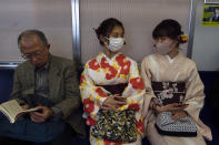 Two women wearing kimono chat in a train in Kyoto, Japan, March 18, 2020. Japanese tourism industry has taken a beating after Beijing banned group tours in late January. Japan's government restricted entry from China and South Korea in early March, then expanded the measures to parts of Europe. (AP Photo/Jae C. Hong)