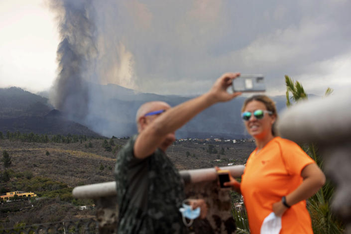 A couple take selfies in front of the eruption of a volcano near El Paso on the island of La Palma in the Canaries, Spain, Monday, Sept. 20, 2021. Lava continues to flow slowly from a volcano that erupted in Spain's Canary Islands off northwest Africa. Officials say they are not expecting any other eruption and no lives are currently in danger. (AP Photo/Gerardo Ojeda)