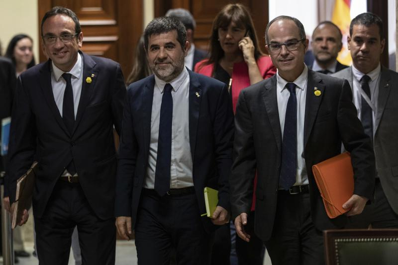 Catalan politicians Josep Rull, left, Jordi Sanchez and Jordi Turull, right, leave after collecting their credentials at the Spanish parliament in Madrid, Spain, Monday, May 20, 2019. The five separatist leaders on trial for Catalonia's 2017 secession attempt who were elected to the Spanish Parliament in April 28 elections have been escorted by police to pick up their official credentials. The five, along with other defendants, are being held in pre-trial jail. They face several years in prison if found guilty of rebellion. (AP Photo/Bernat Armangue)
