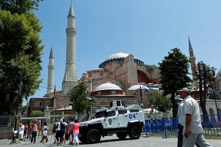 FILE PHOTO: Tourists enter Hagia Sophia as they pass by an armoured police vehicle in the Old City of Istanbul