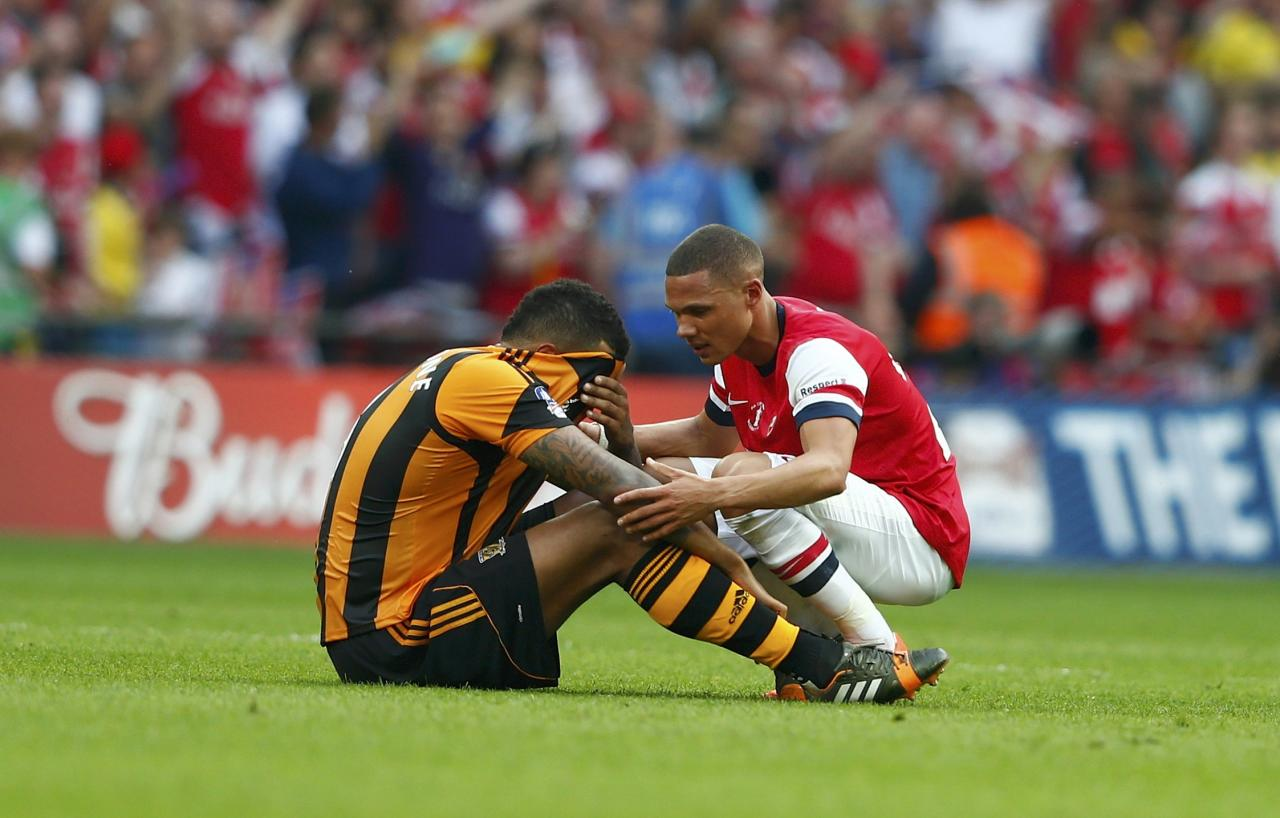 Arsenal's Kieran Gibbs (R) consoles Hull City's Tom Huddlestone, following Arsenal's victory in the FA Cup final soccer match at Wembley Stadium in London, May 17, 2014. REUTERS/Eddie Keogh (BRITAIN - Tags: SPORT SOCCER TPX IMAGES OF THE DAY)