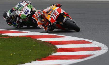 Honda MotoGP rider Marc Marquez (R) of Spain competes with Honda MotoGP rider Scott Redding of Britain during the qualifying session for the British Grand Prix at the Silverstone Race Circuit, central England, August 30, 2014. REUTERS/Darren Staples