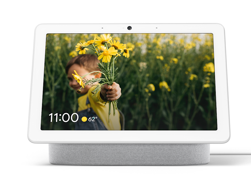 Google Nest Hub with photo on the screen of a little boy with daisies in his hand