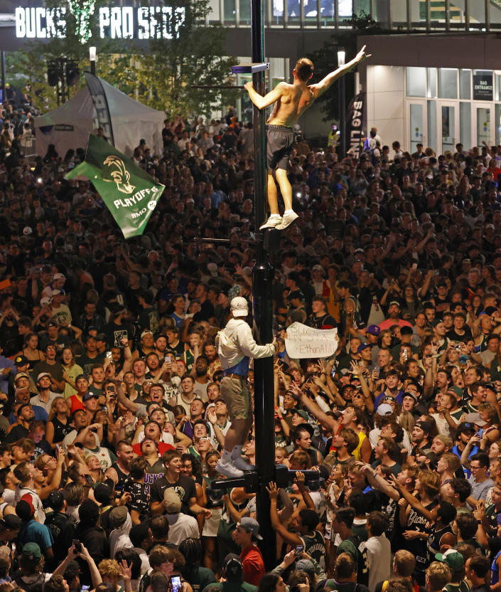 Fans watch Game 6 of the NBA basketball finals game between the Milwaukee Bucks and Phoenix Suns Tuesday, July 20, 2021, in Milwaukee. (AP Photo/Jeffrey Phelps)
