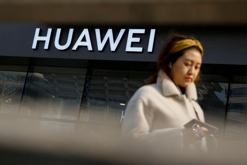 FILE PHOTO: A woman walks past a Huawei shop in Beijing