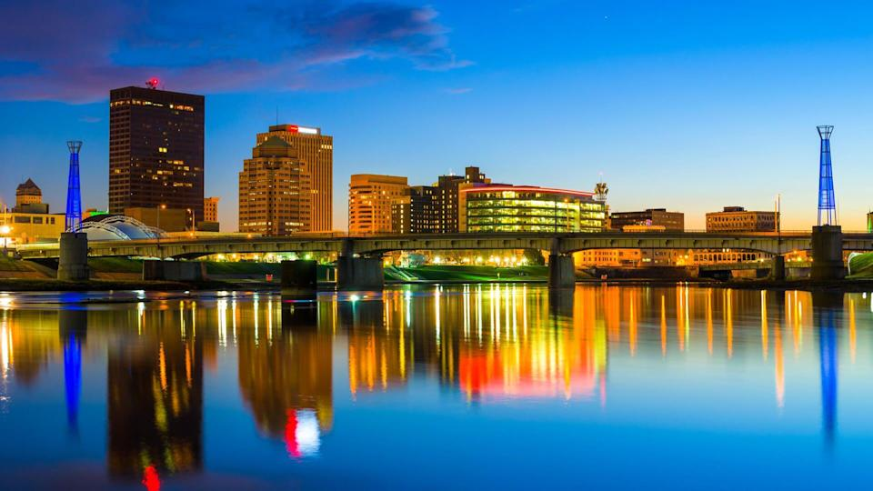 Downtown Dayton skyline with the Miami River and skyline reflections at dusk.