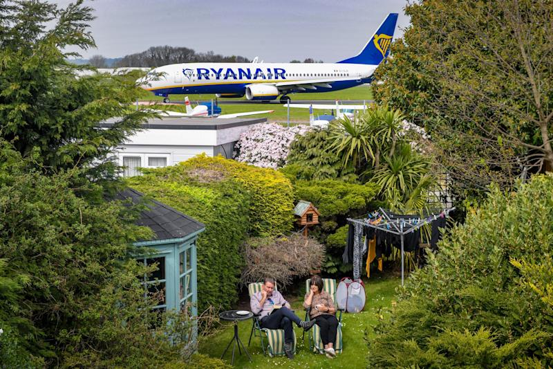 Ms Marchants neighbours, Alex and June Carr in their garden which backs on to Southend Airport in Essex. (SWNS)