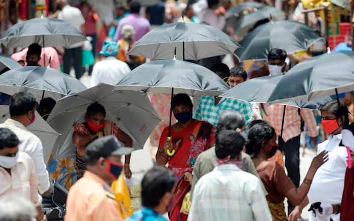 People hold umbrellas distributed by volunteers to maintain social distancing in a market in Chennai - AFP