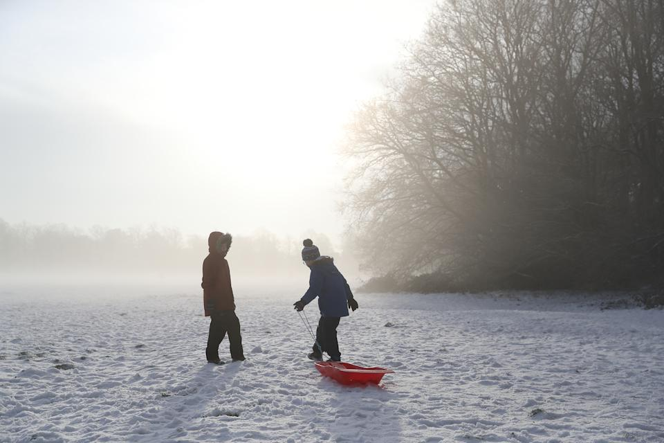 Two children drag a sledge across Knutsford Heath in Cheshire after overnight temperatures dropped below freezing. (PA Images via Getty Images)
