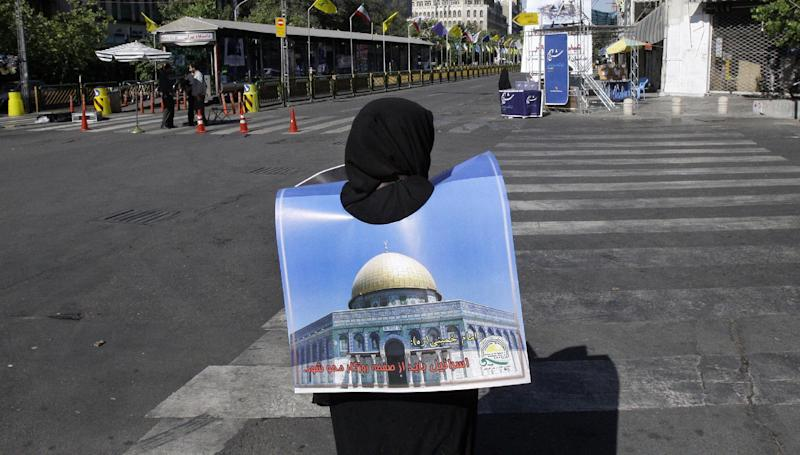 A female Iranian demonstrator holds a poster showing Jerusalem's Dome of the Rock mosque prior to start of an annual pro-Palestinian rally, marking Quds (Jerusalem) Day, on the last Friday of the holy month of Ramadan, at the Enqelab-e-Eslami (Islamic Revolution) St. in Tehran, Iran, Friday, Aug. 17, 2012.(AP Photo/Vahid Salemi)