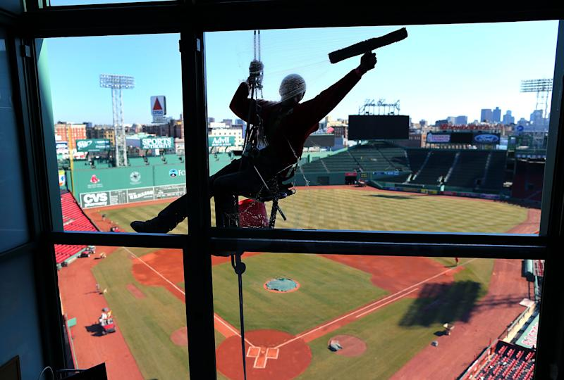 BOSTON - APRIL 3: The grounds crew puts the final touches on their preparations for opening day at Fenway Park, April 3, 2014. Window washer Abi Santos is suspended over the press boxes as he cleans their windows. (Photo by John Tlumacki/The Boston Globe via Getty Images)