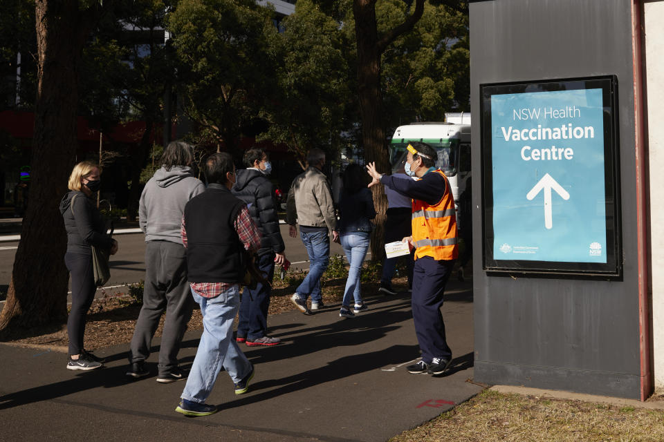SYDNEY, AUSTRALIA - JULY 15: People queue up at the New South Wales Health mass vaccination hub in Homebush on July 15, 2021 in Sydney, Australia. Lockdown restrictions have been extended for at least a further two weeks as NSW continues to record new community COVID-19 cases. Residents of Greater Sydney, the Blue Mountains, the Central Coast and Wollongong are subject to stay-at-home orders with people are only permitted to leave their homes for essential reasons. Essential reasons include purchasing essential goods, accessing or providing care or healthcare, essential work, education or exercise. Exercise is restricted to within the local government area and no further than 10km from home and with a maximum of two people per group. Browsing in shops is prohibited and only one person per household can leave home for shopping per day. Outdoor public gatherings are limited to two people, while funerals are limited to 10 people only. The restrictions are expected to remain in place until 11:59pm on Friday 30 July. (Photo by Brook Mitchell/Getty Images)