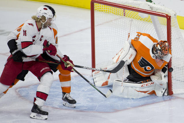 Philadelphia Flyers' Carter Hart, right, blocks a shot as Carolina Hurricanes' Jordan Staal looks on during the first period of an NHL hockey game, Tuesday, Nov. 5, 2019, in Philadelphia. (AP Photo/Matt Slocum)