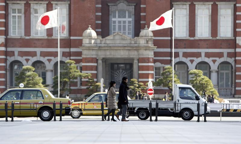 Pedestrians walk under Japan's national flags outside the Tokyo Station