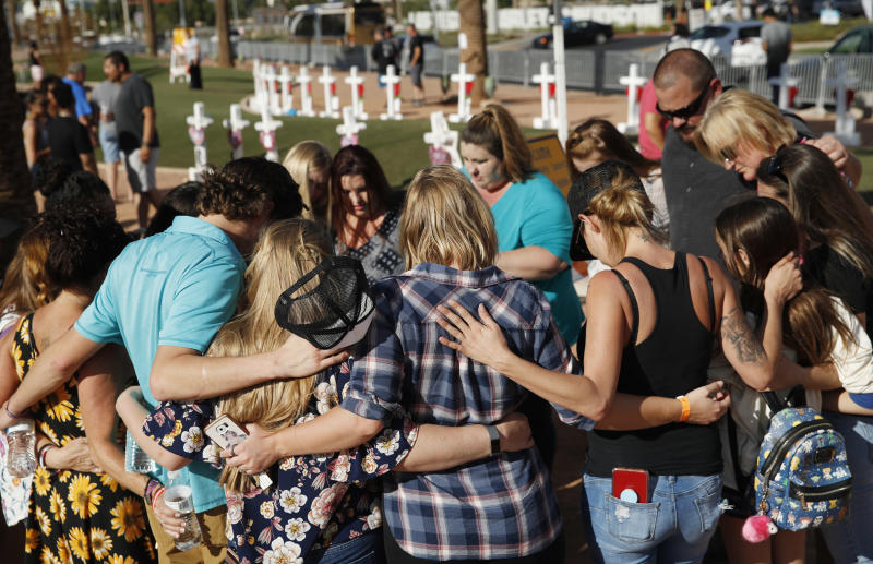 FILE - In this Sept. 30, 2018 file photo people pray at a makeshift memorial for victims of the Oct. 1 2017 mass shooting in Las Vegas. The federal government is allocating nearly $17 million to help people affected by the Las Vegas Strip mass shooting that became the deadliest in the nation's modern history, acting U.S. Attorney General Matthew Whitaker said Friday, Nov. 30, 2018. (AP Photo/John Locher, File)