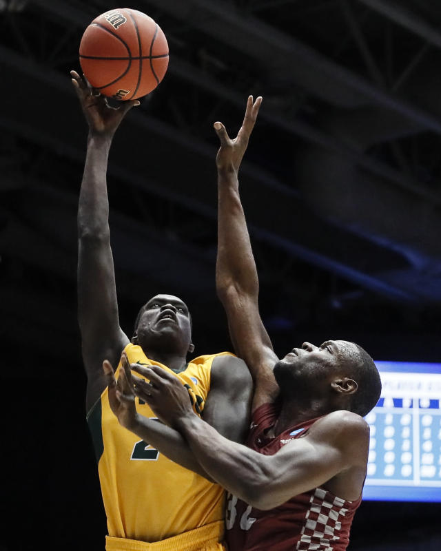 North Dakota State's Deng Geu, left, shoots against North Carolina Central's Raasean Davis, right, during the second half of a First Four game of the NCAA men's college basketball tournament Wednesday, March 20, 2019, in Dayton, Ohio. (AP Photo/John Minchillo)