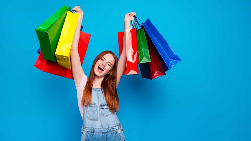 young excited woman holding shopping bags