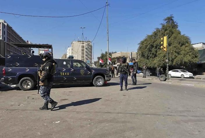 Security forces gather at the site of a deadly bomb attack in Baghdad's bustling commercial area, Iraq, Thursday, Jan. 21, 2021. Twin suicide bombings hit Iraq's capital Thursday killing and wounding civilians, police and state TV said. (AP Photo/Hadi Mizban)