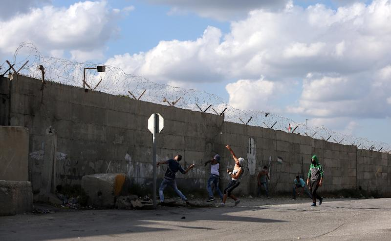 Palestinians hurl rocks above a wall during clashes with Israeli soldiers in the West Bank Palestinian town of Tulkarem on October 8, 2015 (AFP Photo/Jaafar Ashtiyeh)
