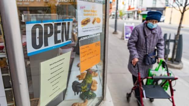 A pedestrian using a walker passes a bakery on Ottawa's Bank Street in late April 2021.