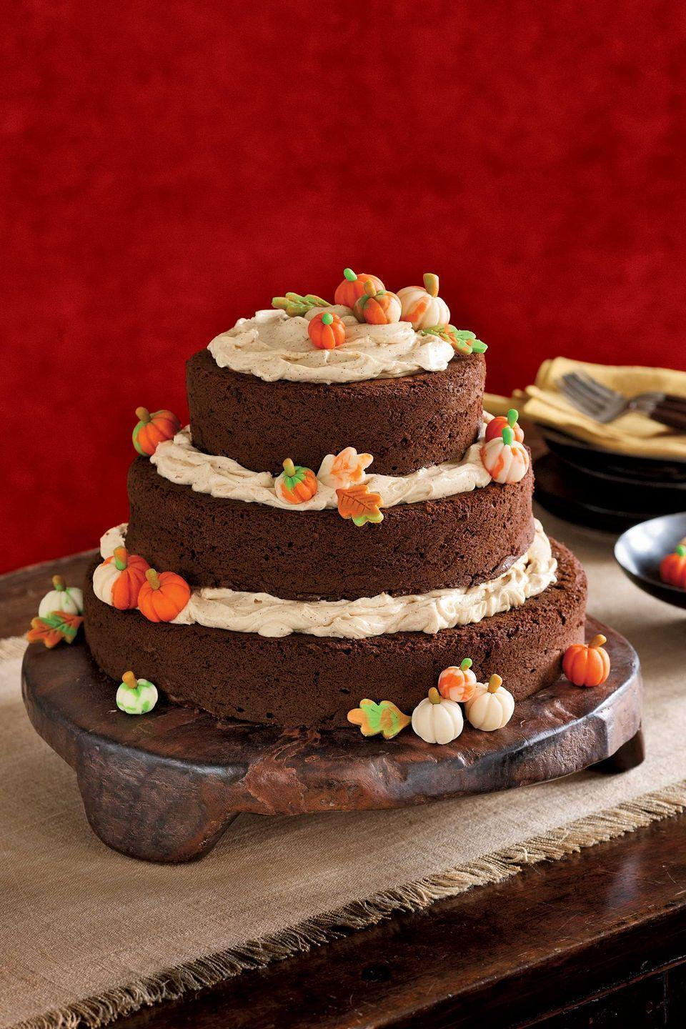 """<p>This towering pumpkin patch begins as three cakes in graduated sizes, with three generous layers of buttercream that escape temptingly toward the tiers' edges. The pumpkins and leaves, both made of tinted marzipan, needn't be perfect to be appreciated, so invite young helpers to assist.</p><p><strong><a href=""""https://www.countryliving.com/food-drinks/recipes/a842/pumpkin-spice-pecan-cake-35/"""" rel=""""nofollow noopener"""" target=""""_blank"""" data-ylk=""""slk:Get the recipe"""" class=""""link rapid-noclick-resp"""">Get the recipe</a>.</strong> </p>"""