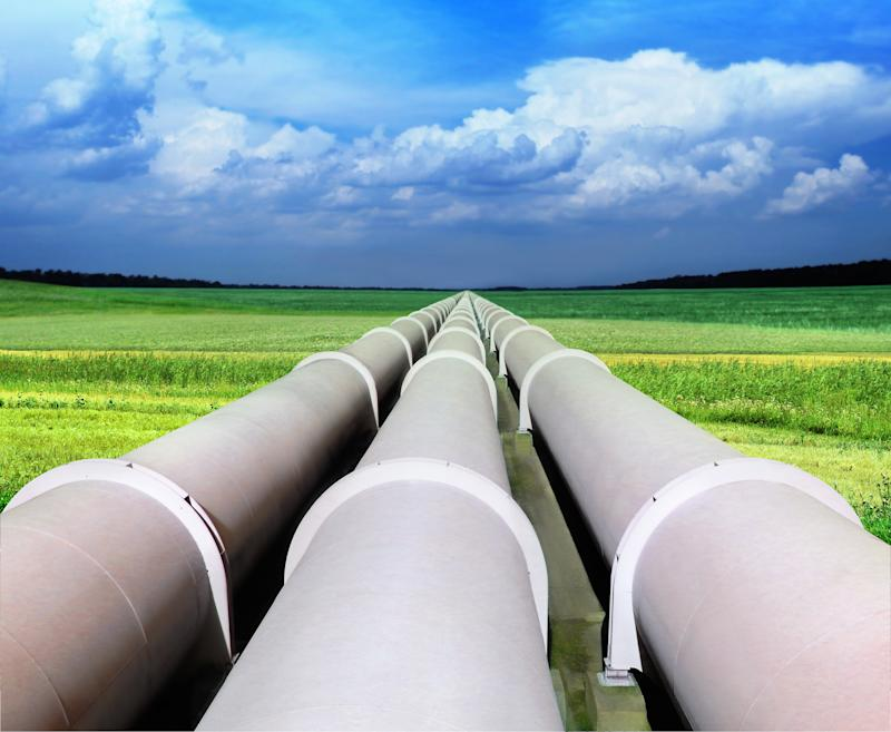 Three gray pipelines in a green field with blue sky and white, puffy clouds above.