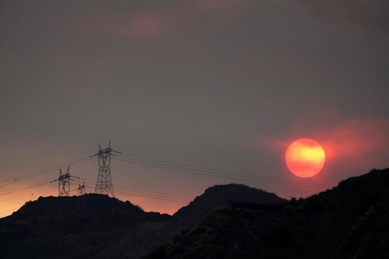 The sun sets through smoke created by the Ranch Fire, Thursday, Aug. 13, 2020, in Azusa, Calif. Heat wave conditions were making difficult work for fire crews battling brush fires and wildfires across Southern California.