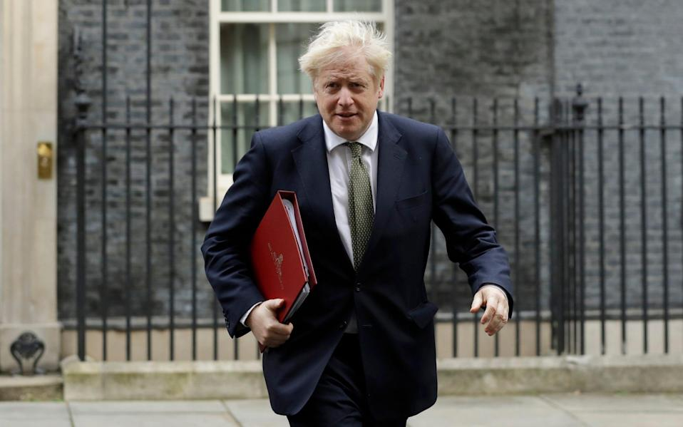 British Prime Minister Boris Johnson walks from 10 Downing Street to a meeting with his ministers at the Foreign Office, in London - Matt Dunham/AP