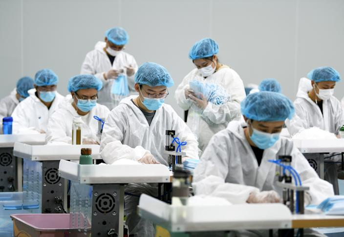 Employees work on a production line of surgical masks for export, at a railway equipment manufacturing company in Nanchang, Jiangxi province, China April 8, 2020. Picture taken April 8, 2020. (China Daily via Reuters)