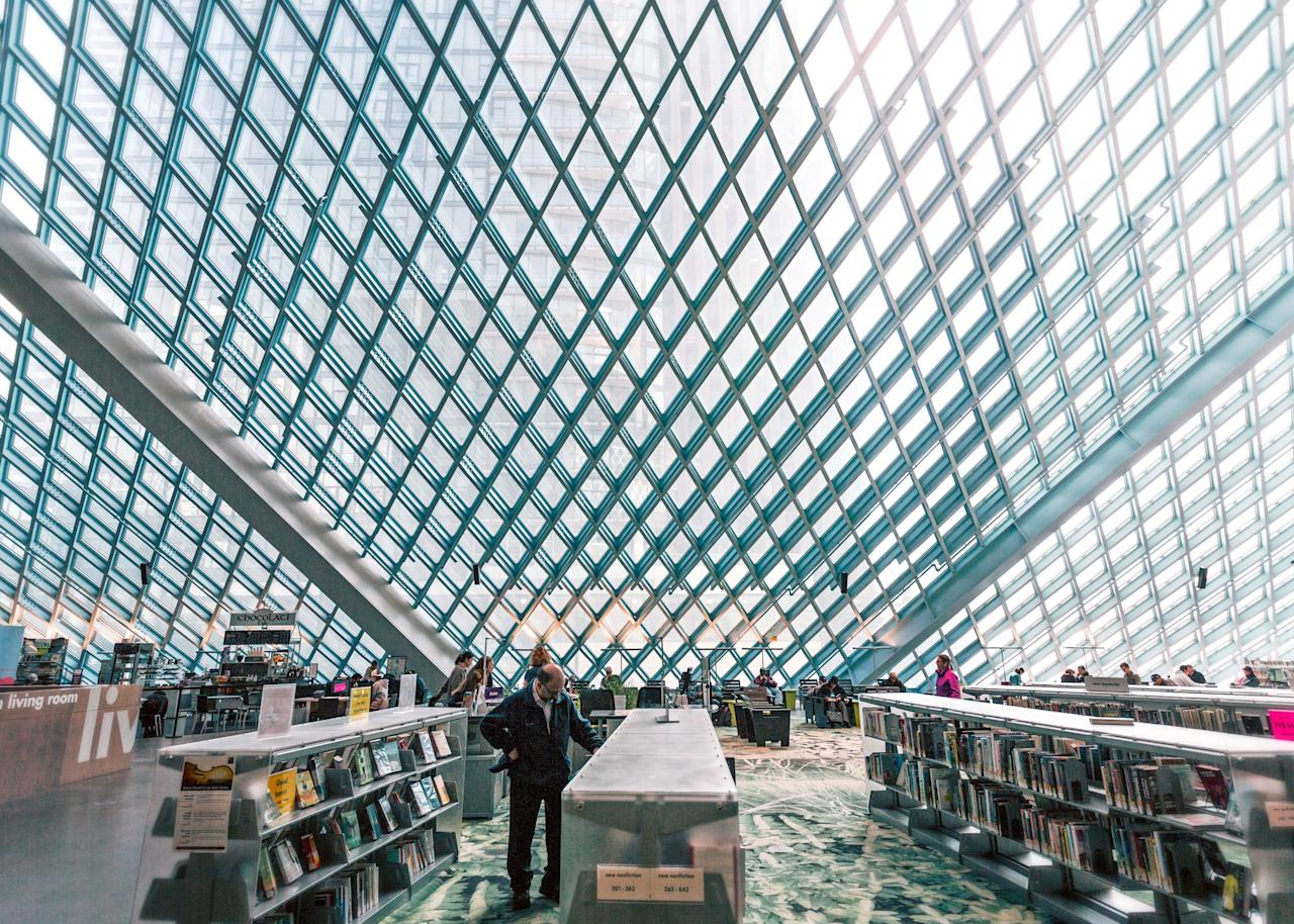 """Designed by Pritzker Prize-winning Dutch architect Rem Koolhaas, the <a href=""""https://www.cntraveler.com/activities/seattle/seattle-public-library-central-library?mbid=synd_yahoo_rss"""">Seattle Public Library's central branch building</a> juts out of the downtown skyline. The glass-and-steel edifice stands 11 stories tall, and due to its location on a hill you can enter and exit on different floors. The inside pops thanks to a vivid green color used as a decorative touch on walls and in the elevator—fitting, since Seattle's nickname is """"the Emerald City."""" Head to the 10th-floor reading room to take in views of the city, including Elliott Bay."""