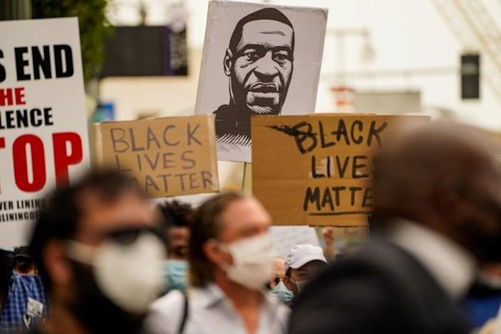 """A sign with the likeness of George Floyd is seen at a protest outside L.A. City Hall. <span class=""""copyright"""">(Kent Nishimura / Los Angeles Times)</span>"""